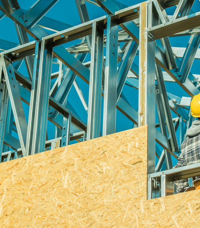 Construction Site Worker in Yellow Hard Hat. Attachment Skeleton Steel Building Elements. Industrial Theme.